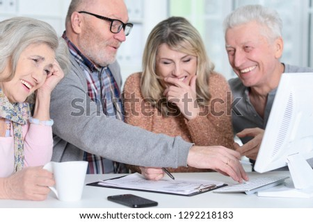 two senior couples sitting at table and working