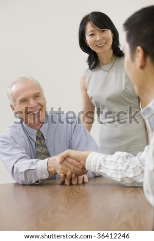 Two senior executives congratulating junior team member.