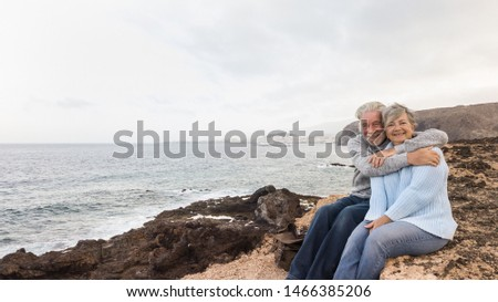 Two senior people sitting on the cliff of the ocean and looking at camera Hugging and smiling. Morning soon outside, ready for un healthy excursion. Vacation and happiness