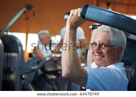 Two senior people working out in a gym with fitness coach