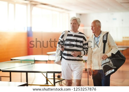 Two senior sportsmen with bags having talk while moving to their tennis table