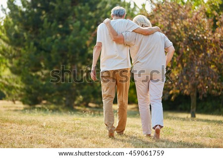 Two seniors in love walking in the nature in summer