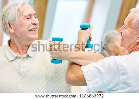 Two seniors playfully test their powers with dumbbells in the fitness center