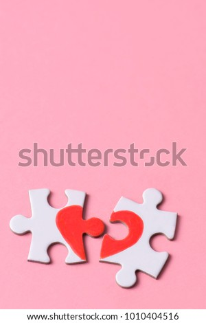 two separated pieces of a puzzle which together form on a pink background with a blank space on top, depicting the idea of rupture or cooperation