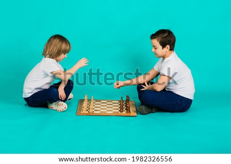 Two serious boy playing chess in studio, blue background Stok fotoğraf ©