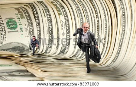 Two serious businessmen running in dollar tunnel