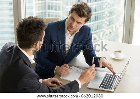 Two serious businessmen using laptop and discussing new project at office, developing strategy for online business, explaining sharing ideas, preparing presentation, having brainstorming session