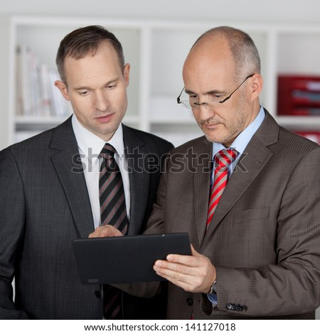 Two serious businessmen working with tablet computer