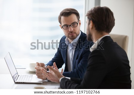 Two serious caucasian men in suits discussing or planning business issues in the office. Colleagues or client and consultant are sitting at the table next to each other and talking.