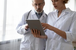 Two serious doctors team discuss patient diagnosis data hold digital tablet computer technology. Senior male doctor and young female nurse working together, talking, using modern tech app in hospital.