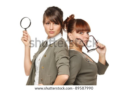 Two serious girls standing with magnifying glass and old fashioned eyeglasses, isolated on white background