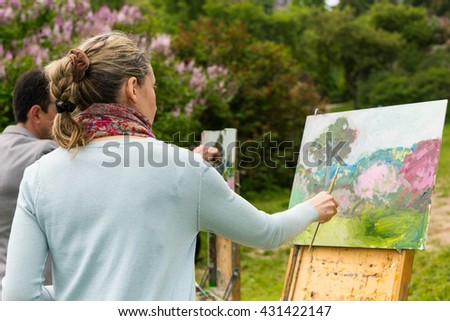 Two serious professional artists in the process of painting standing in front of their easels outdoors with background of beautiful trees