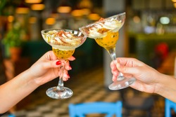 Two servings of chocolate cream dessert in tall martini glasses. Two young women holding glasses with dessert over blurred restaurant background, selective focus. Cheers, leisure time with friends.