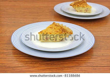 Two servings of quiche lorraine on a blue striped plates and a wood tabletop.