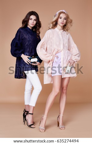 Two sexy blonde and brunette woman friend or rival beautiful face wear silk blouse casual clothes for every day accessory and jewelry fashion model style makeup studio handbag summer collection. #635274494