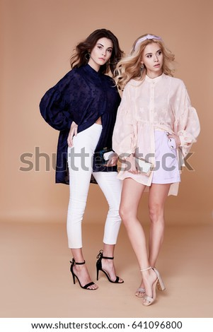 Two sexy blonde and brunette woman friend or rival beautiful face wear silk blouse casual clothes for every day accessory and jewelry fashion model style makeup studio handbag summer collection. #641096800