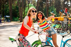Two sexy cool, cute hipster girl ride on a green and blue bicycles, sunglasses, colorful casual wear, best friends, laughing, having fun, play the fool, smiling, blonde and brunette, best friends
