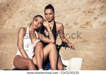 Two sexy female twins posing in fashionable swimsuit over sand, sunny summer day. #1162230520