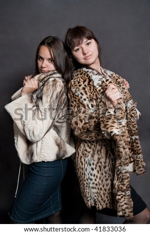 two sexy girls in fur coat on gray background