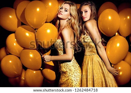 Two sexy girls in golden balloons. Celebrating.