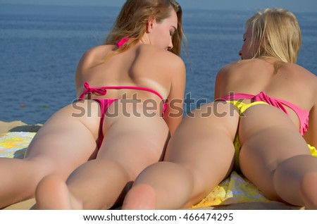 Two sexy girls in thongs on the beach sunbathing.