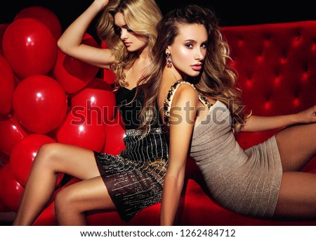 Two sexy girls on lounge. Celebrating.