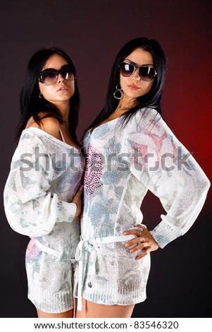 Two sexy girls posing on dark background