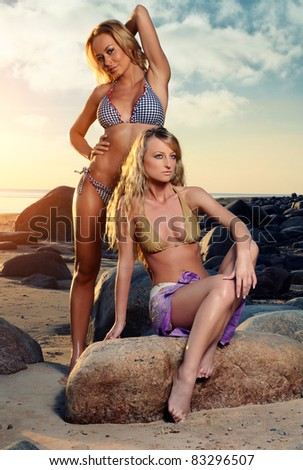 Two sexy girls posing on the beach