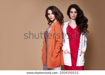 Two sexy glamour fashion model business woman long curly brunette hair wear silk dress and wool cardigan friend party style or date accessory and luxury jewelry catalog of clothes studio background.
