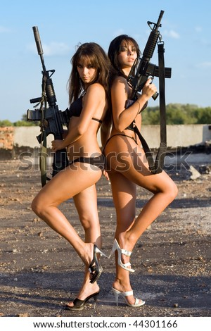 Two sexy naked women posing with rifles