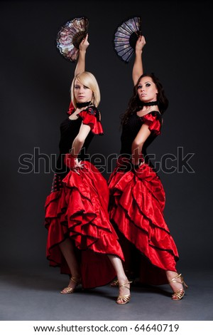 two sexy spanish women dancing over dark background