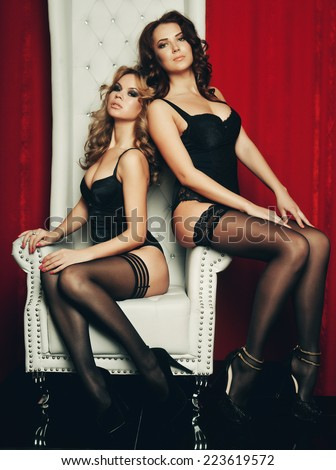 two sexy women in lingerie on white throne. Striptease. #223619572