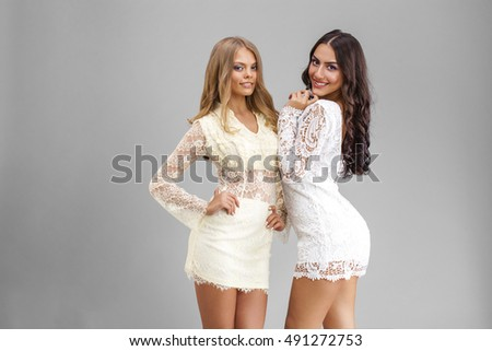 Two sexy women in white sexy dress, isolated on gray background #491272753
