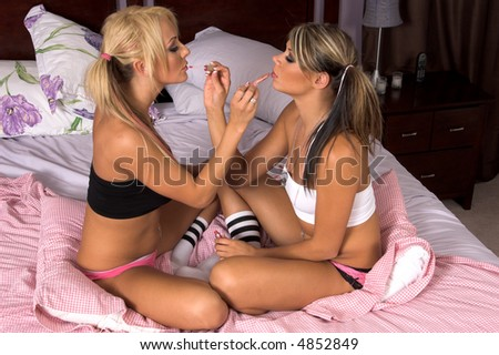stock photo two sexy young women sitting cross legged on the bed and applying each others makeup while at a 4852849 Woman Hid In Woods With Daughters For Two Days To Escape Abuse