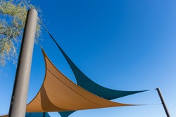 Two shade canopies against a clear blue sky