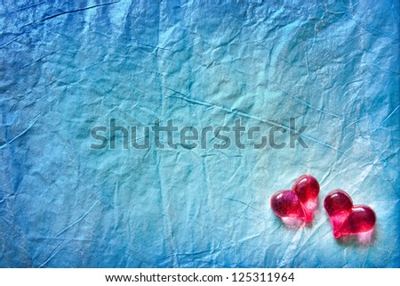 Two shining hearts over blue wrapping paper background
