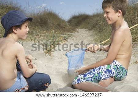 two shirtless boys playing with fishing net in sand dunes