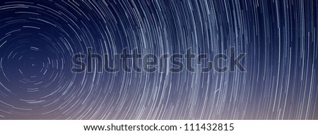 Two shooting stars streak across a long exposure star trail revolving around Polaris or the Northern Star