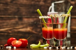 Two shot glasses with cocktail Bloody Mary, celery, spices and ripe tomatoes on dark wooden background with copy space