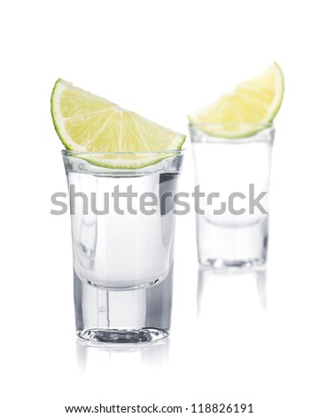 Two shots of vodka and lime slice. Isolated on white background