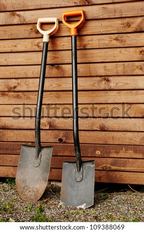 Two shovels against wooden wall