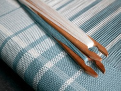 Two shuttles with turquois and white yarn are on the weaving loom. Woven striped fabric