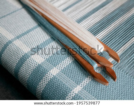 Two shuttles with turquois and white yarn are on the weaving loom. Woven striped fabric Stock foto ©