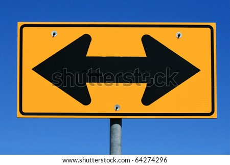 two sided black and yellow road sign designating two way traffic with a blue sky background - stock photo