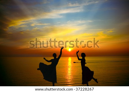 Two silhouette dancers in front of the sunset