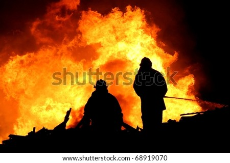 Two silhouetted firemen fighting a large fire