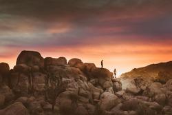 Two Silhouettes of Men Walking Along Boulders in High Desert - Sunset in Joshua Tree National Park
