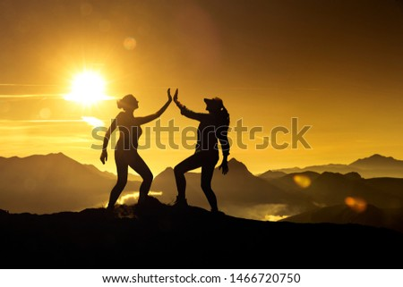 Two Silhouettes of the same woman giving herself high five on a mountain peak at sunrise, composed together in image editing Stok fotoğraf ©