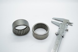two silver roller bearings standing next to a caliber isolated on a white background