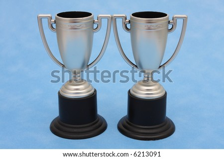 Two silver trophies on blue background